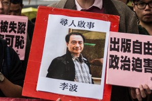 "In this picture taken on January 3, 2016, a protestor holds up a missing person notice for Lee Bo, 65, the latest of five Hong Kong booksellers from the same Mighty Current publishing house to go missing, as they walk towards China's Liaison Office in Hong Kong. Britain confirmed on January 5 that one of five missing Hong Kong booksellers feared detained by Chinese authorities is a UK citizen, saying it was ""deeply concerned"" over the disappearances. AFP PHOTO / ANTHONY WALLACE / AFP / ANTHONY WALLACE (Photo credit should read ANTHONY WALLACE/AFP/Getty Images)"